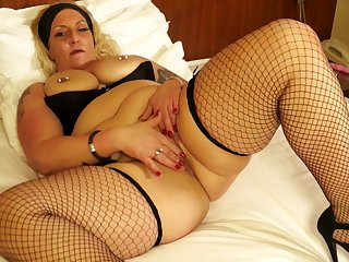 Tattooed and pierced blonde Ddesire fingers her pussy in stockings